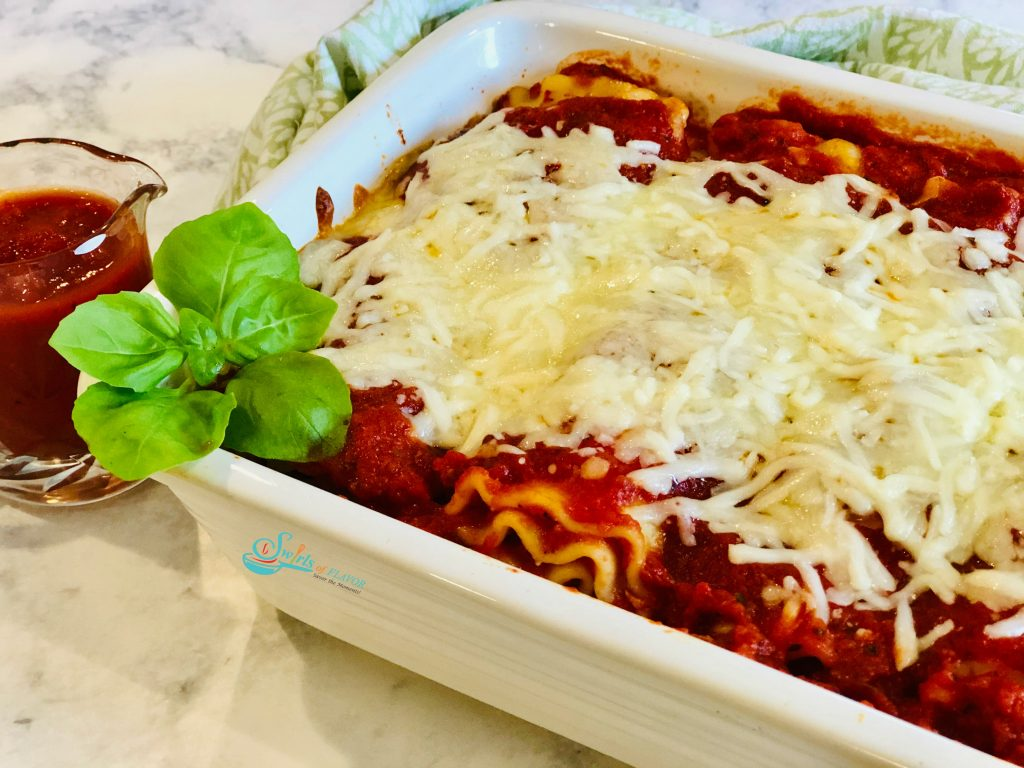 Lasagna roll ups in a white baking dish with fresh basil sprig and sauce in a small pitcher