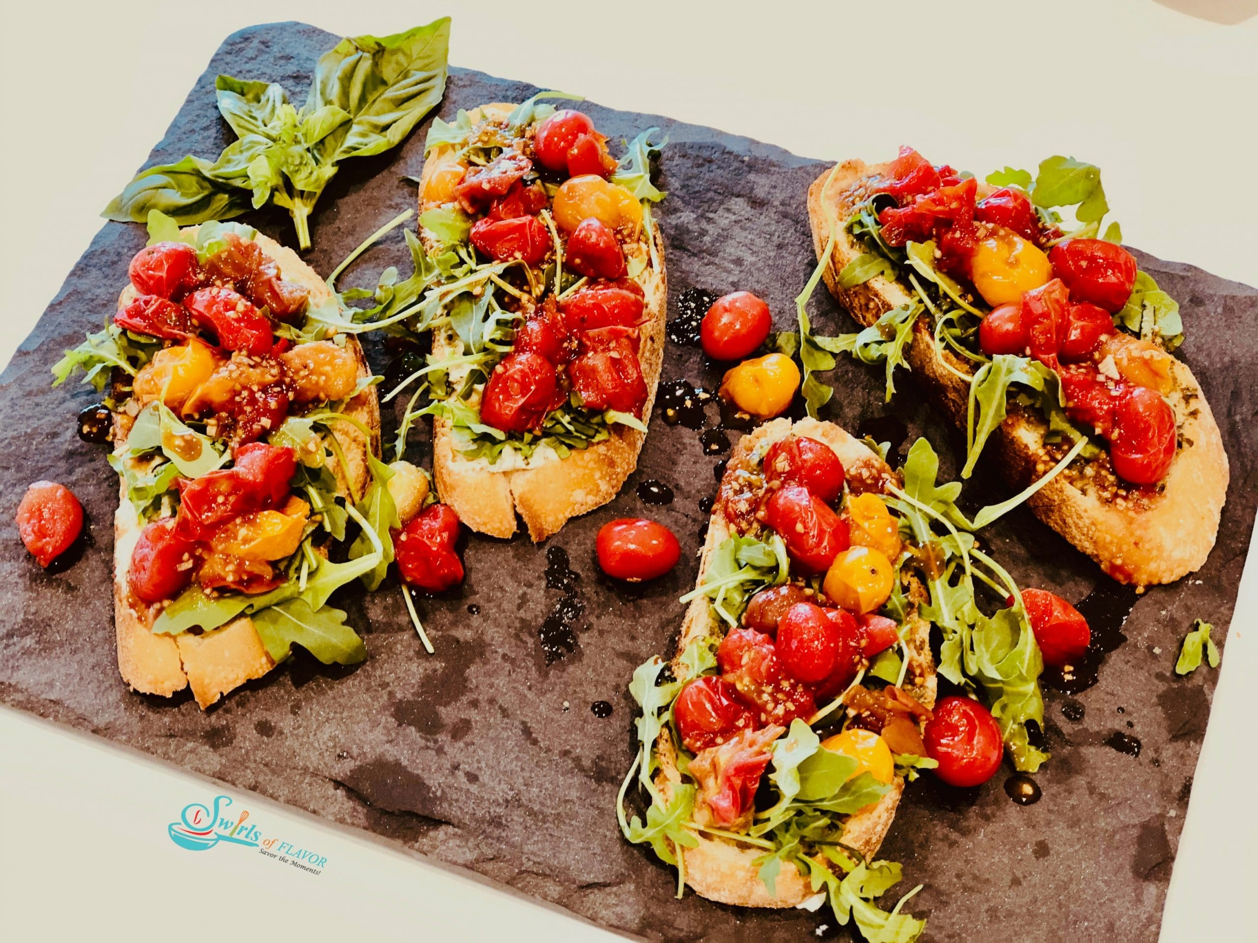 Four toasts topped with tomatoes and arugula on a grey slate