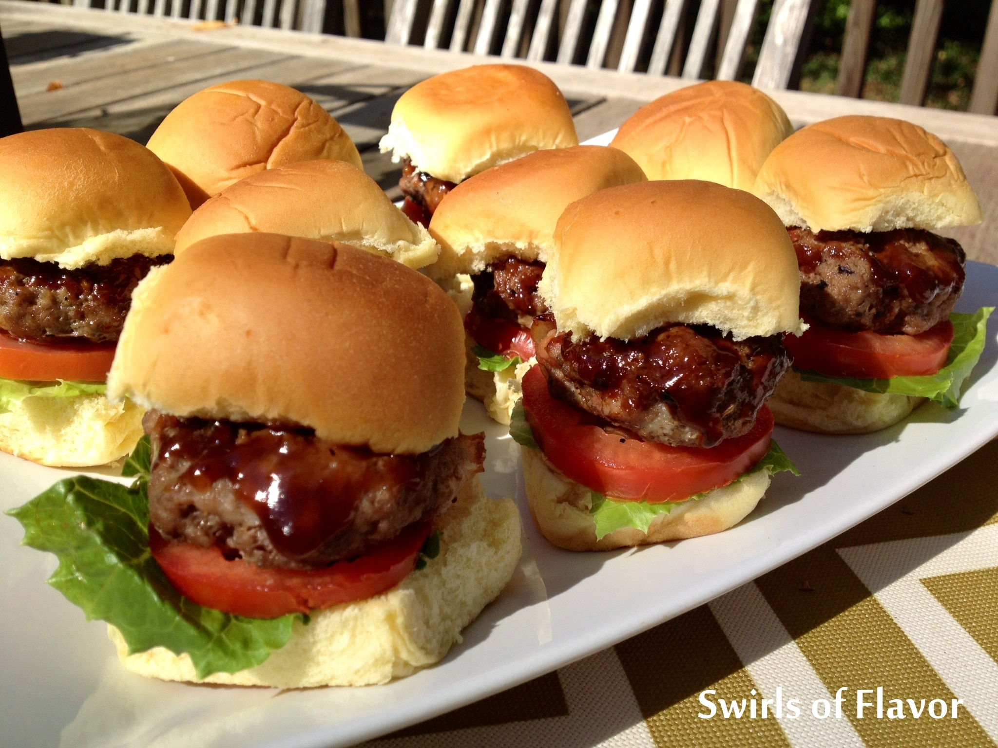 Mini burgers with a barbecue glaze, tomatoes and lettuce on mini rolls on a platter