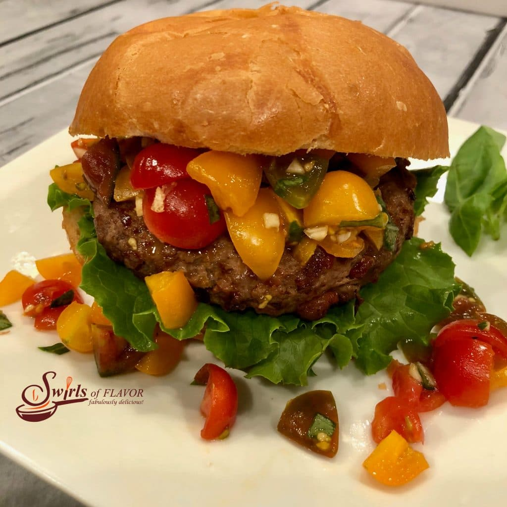 Hamburger with tomato topping on a white dish