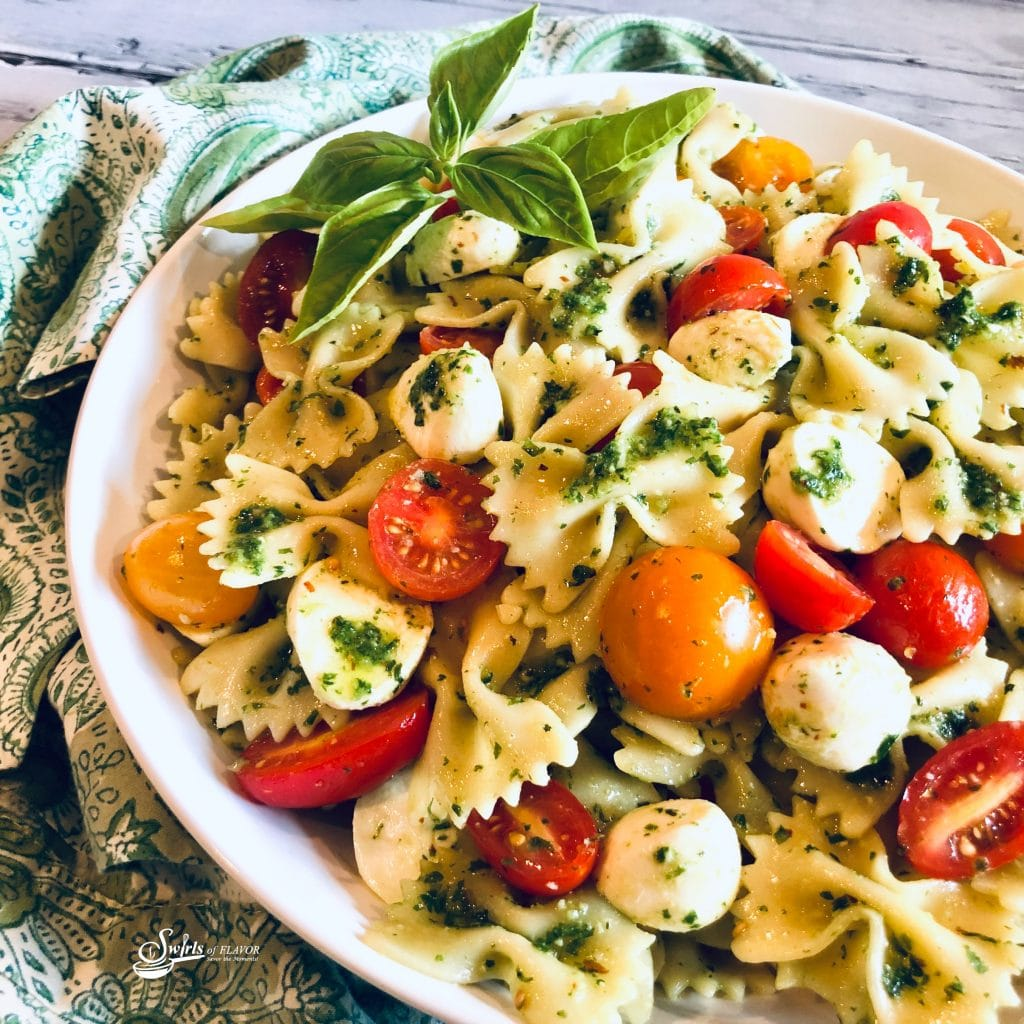 Bow tie pasta salad with tomatoes, mozzarella and pesto in a round white bowl