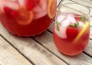 stemless wine glass filled with pink prosecco punch, strawberries and lemon