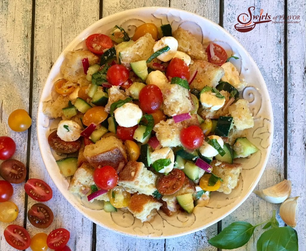 Bread Salad with tomatoes, mozzarella and cucumber in white serving dish
