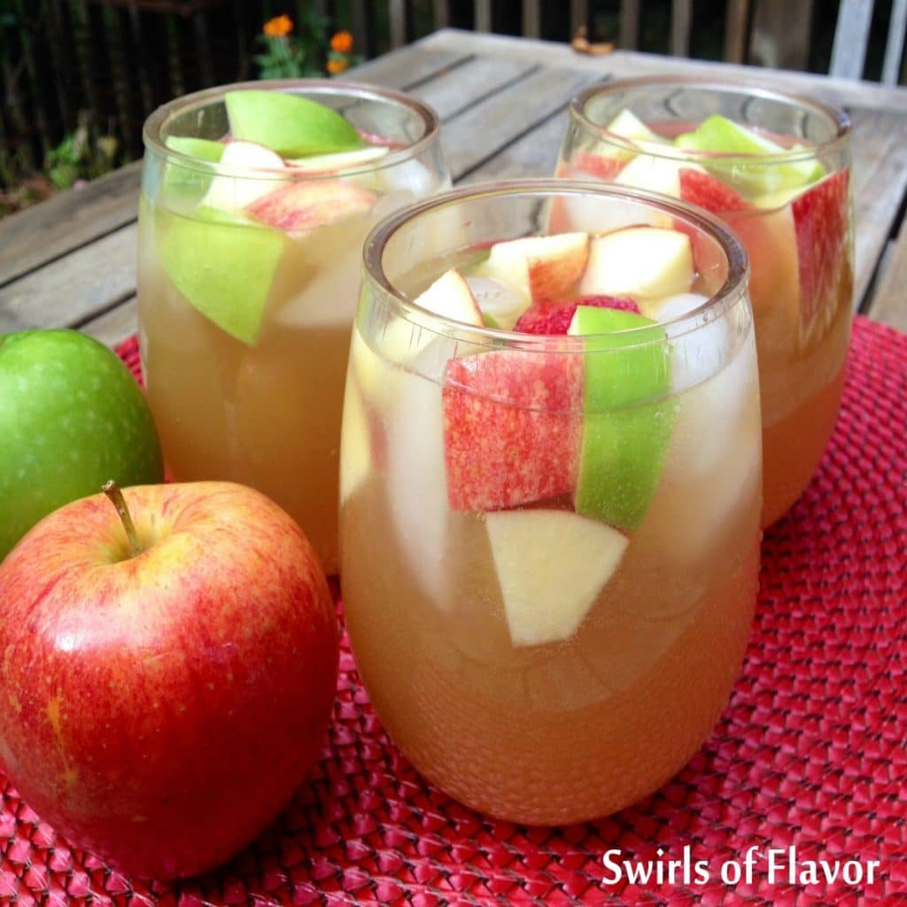 stemless wine glasses filled with apple cider sangria and pieces of apple