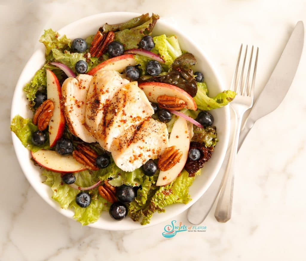 Sliced chicken on bed of greens with apples and pecans