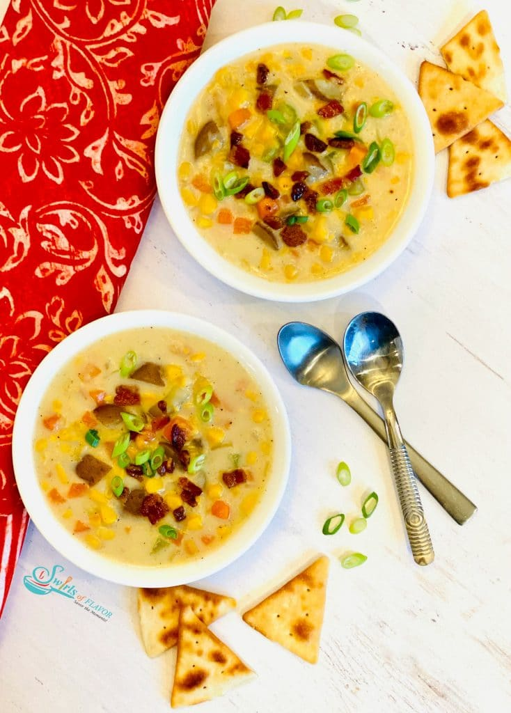 Two bowls of corn chowder topped with bacon and scallions