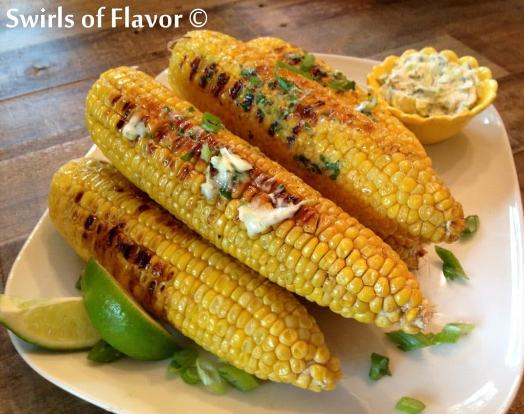 Corn on the cob on plate with seasoned butter and lime wedges