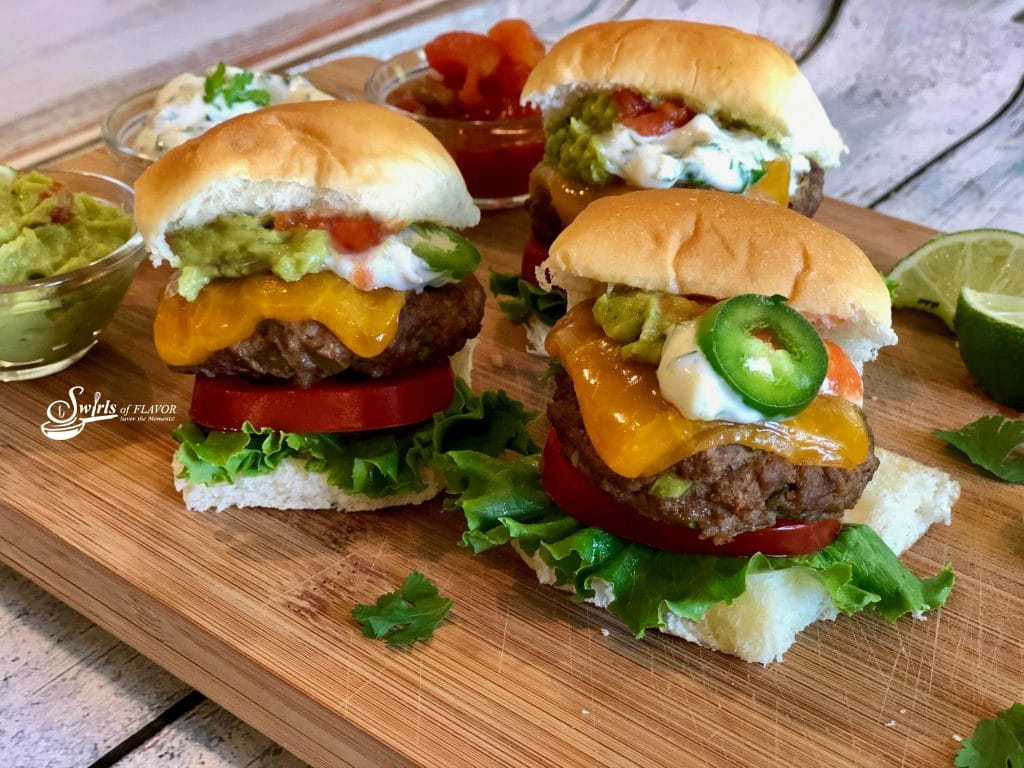 Mini cheeseburgers with cheese, jalapenos and guacamole on a bun with tomato slice and lettuce