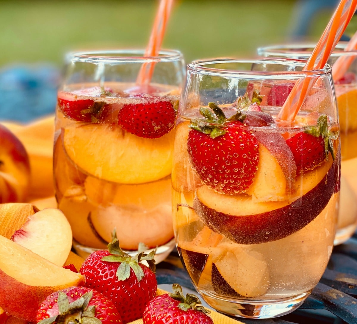 Stemless wine glasses filled with sangria, fresh fruits and straws