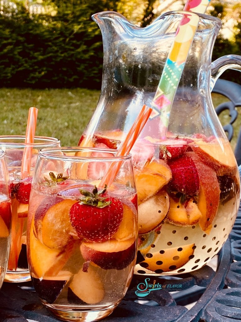 Stemless wine glasses and pitcher filled with peach sangria, fresh fruits and straws