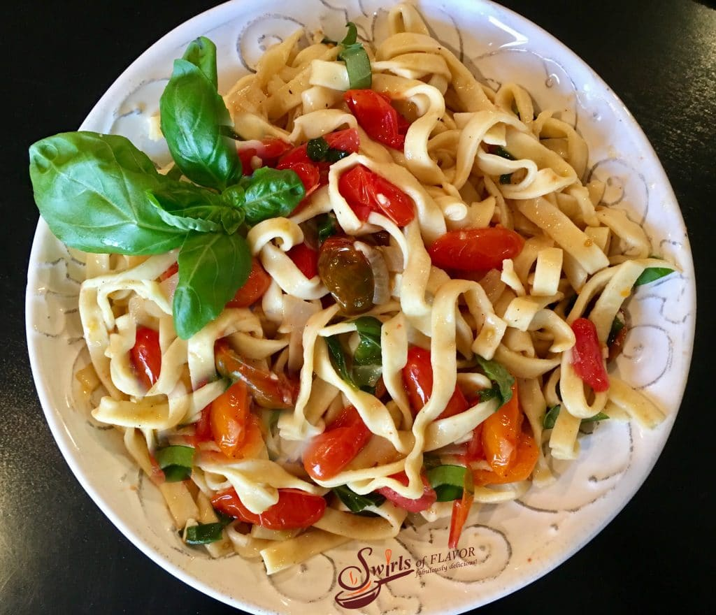 Fettuccine with tomatoes and fresh basil in round white bowl