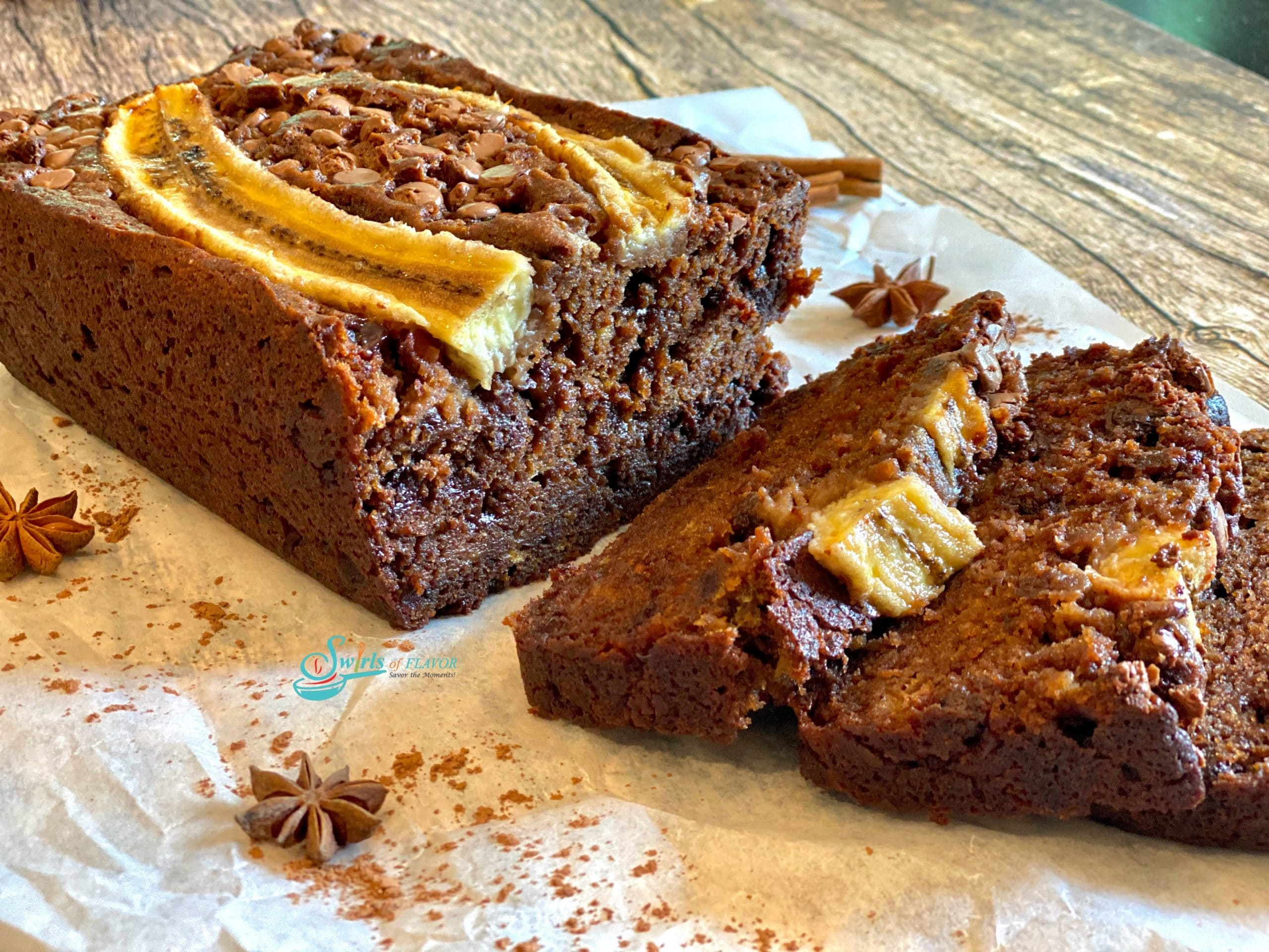 chocolate banana bread with sliced banana on top and slices of bread in front