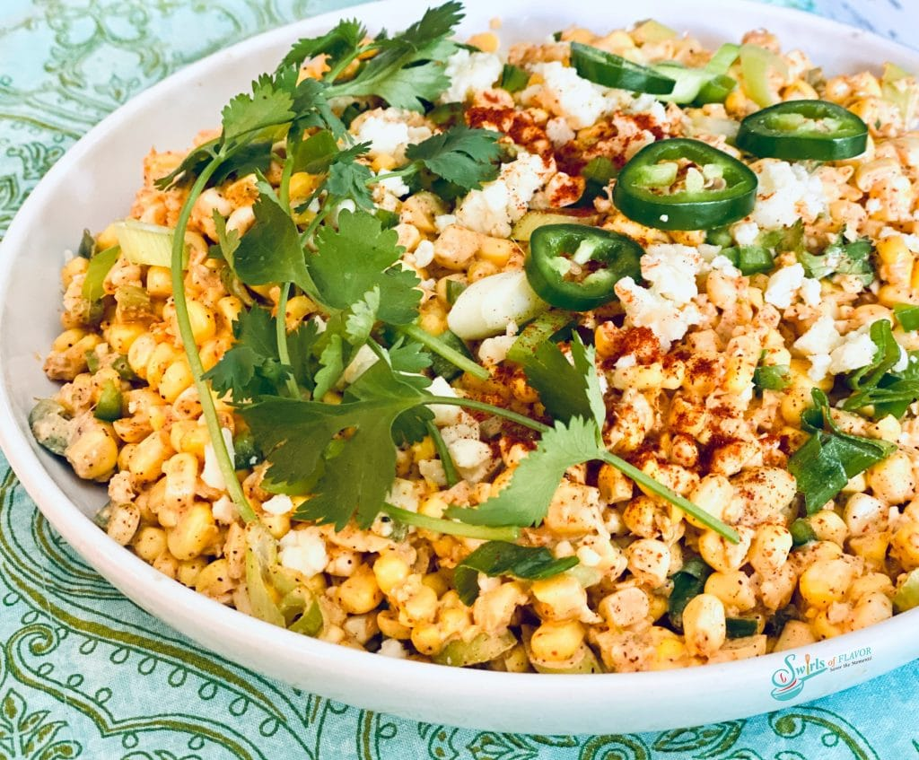 Fresh corn salad with jalapeno, cilantro and cheese in whte bowl