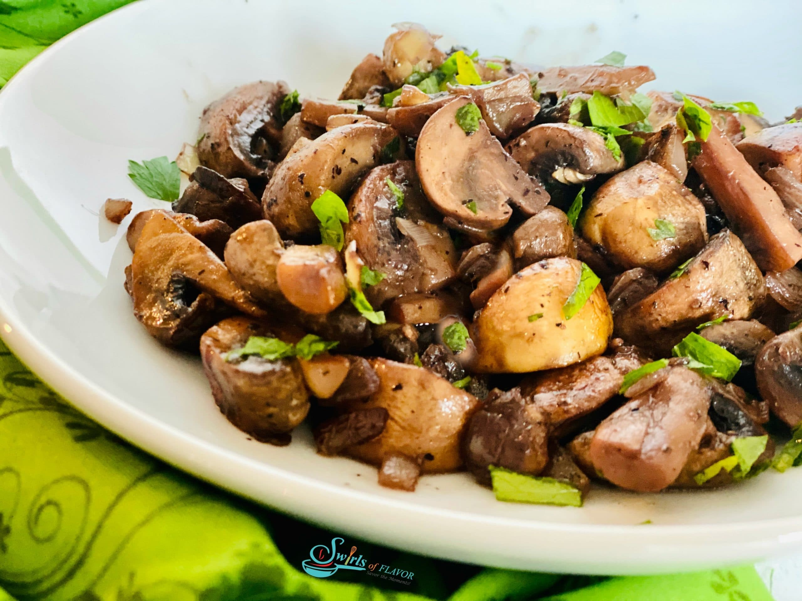 sauteed mushrooms in white dish with parsley