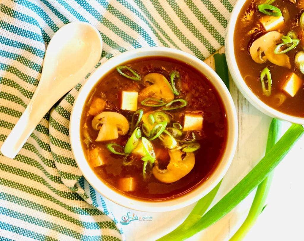 bowls of soup with mushrooms, tofu and scallions