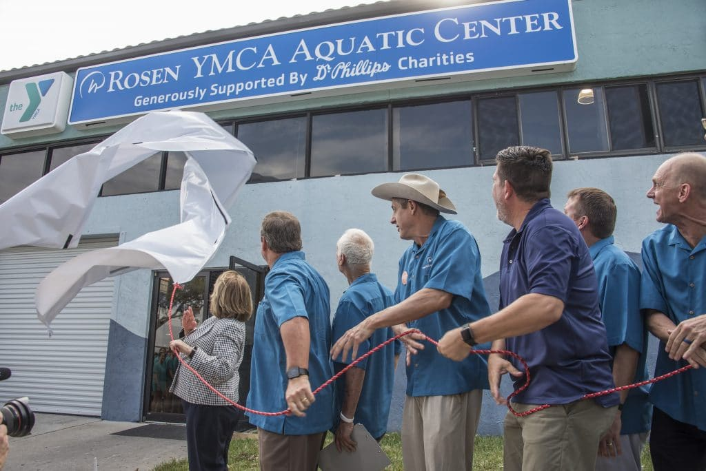 The Harris Rosen Aquatic Center YMCA unveiling. People pulling a tarp off of the new sign