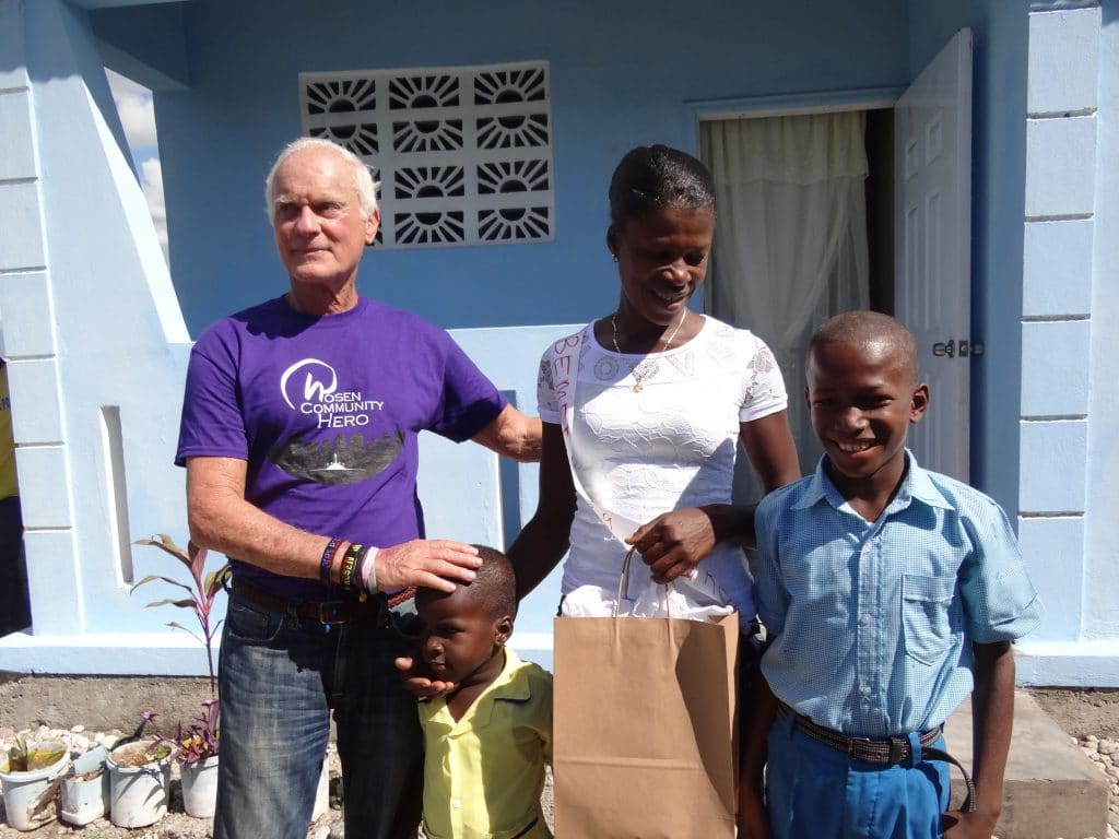 Mr. Rosen standing with new homeowners in Haiti in front of their house