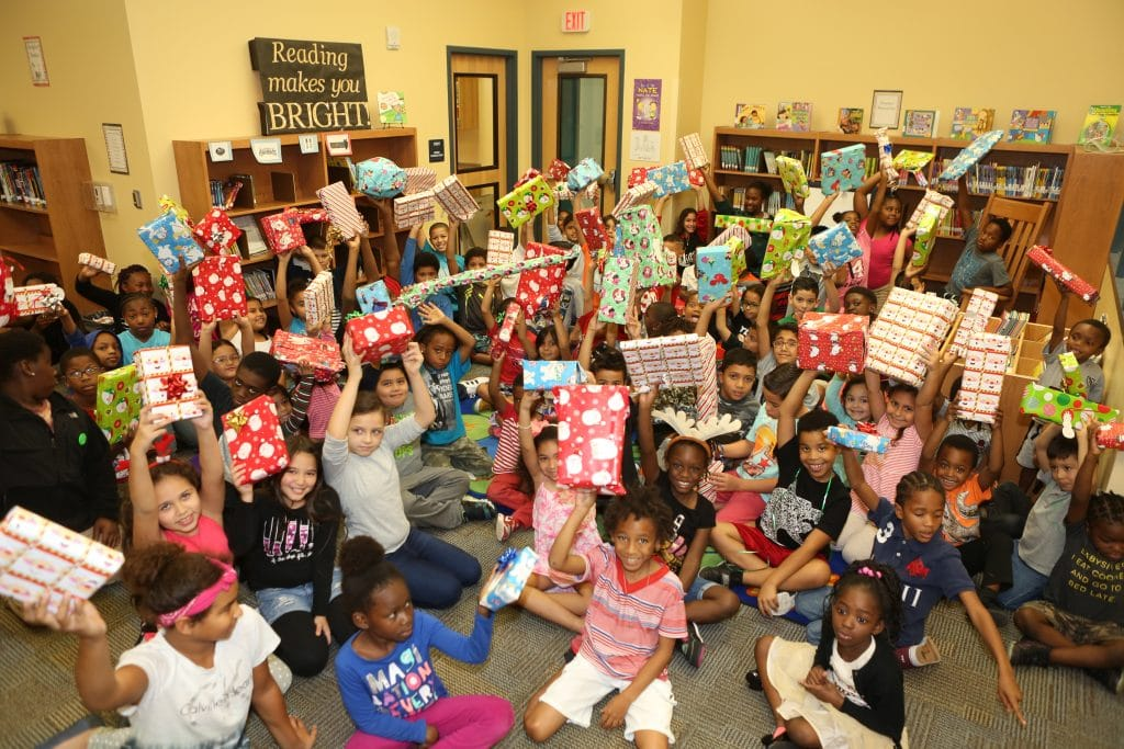 Tangelo Park students showing their Christmas presents in a classroom