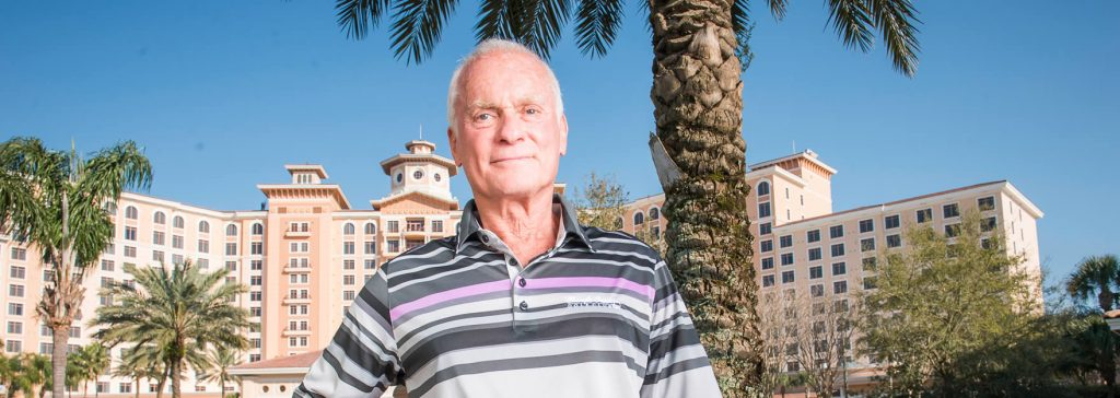 Harris Rosen In front of his hotel with blue skies and palm trees